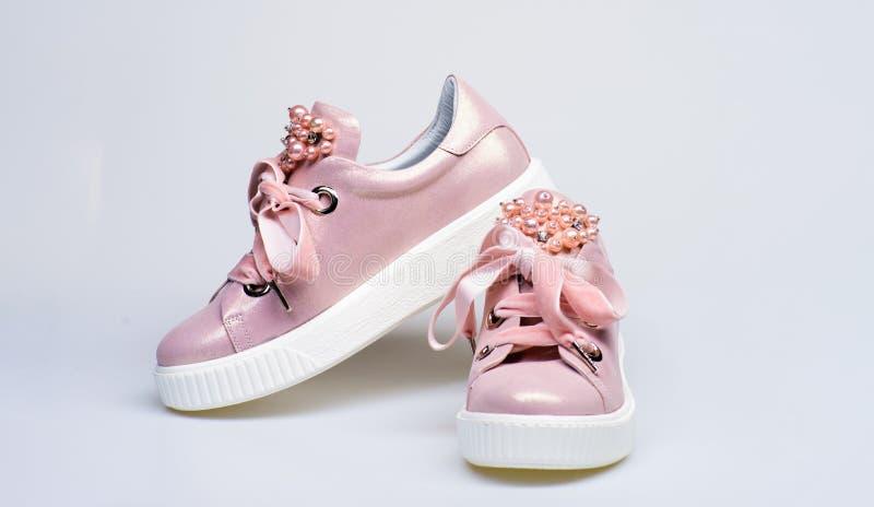 Bezauberndes Turnschuhkonzept Schuhe für die Mädchen und Frauen, die mit Perle verziert werden, bördeln Nette Schuhe auf weißem H lizenzfreies stockbild