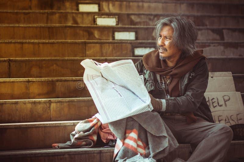 Bezdomna mężczyzny czytelniczego społeczeństwa gazeta na schodku obrazy stock
