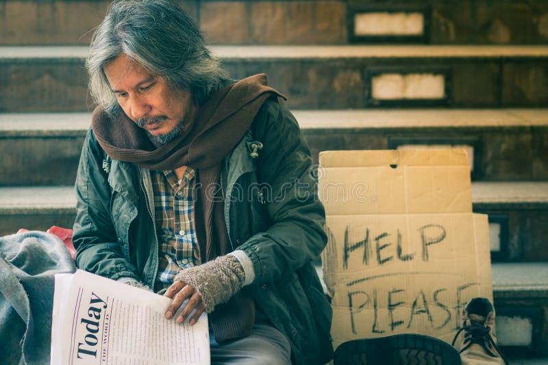 Bezdomna mężczyzny czytelniczego społeczeństwa gazeta na schodku przejście ulica w mieście czekać na dobroć ludzi daje obrazy stock