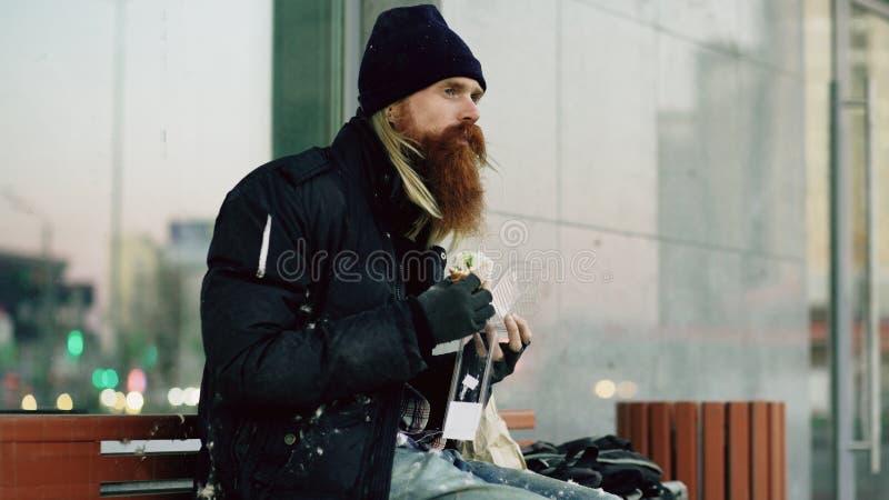 Bezdomna młodego człowieka łasowania kanapka na ławce przy miasto ulicą w wieczór obraz royalty free