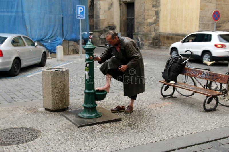 Bezdomna osoba myje jego cieki na ulicie obraz stock