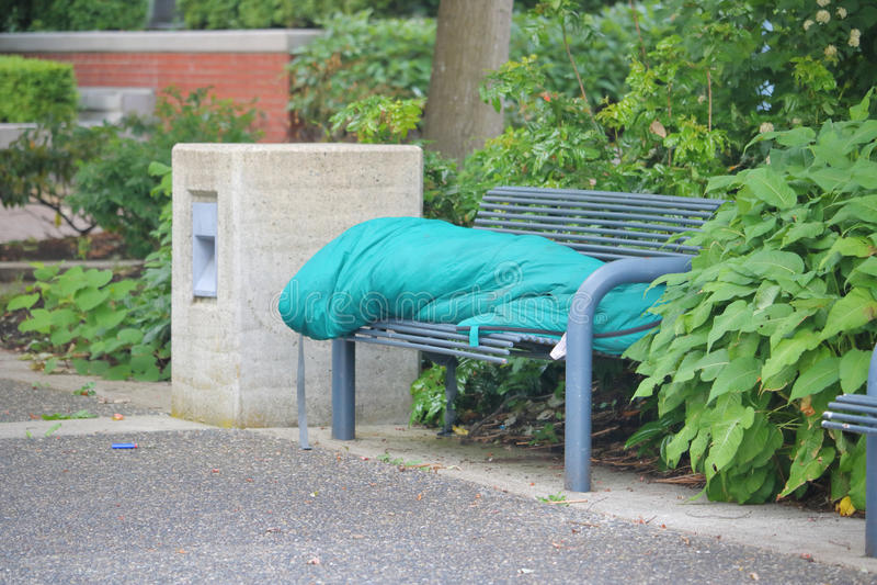 Bezdomna osoba na miasto ławce obraz stock