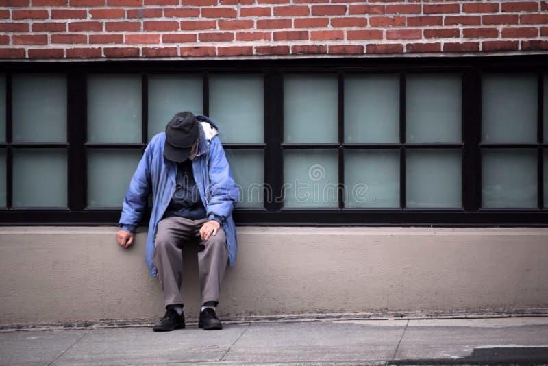 Bezdomnej osoby obsiadanie ścianą obrazy royalty free