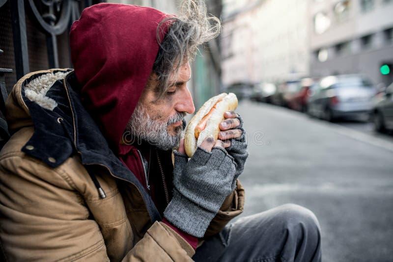 Bezdomny żebraka mężczyzna outdoors w mieście mienie i wąchać hot dog, zdjęcie stock