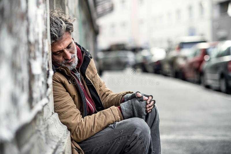 Bezdomny żebraka mężczyzna siedzi outdoors w mieście pyta dla pieniądze darowizny, śpiący fotografia stock