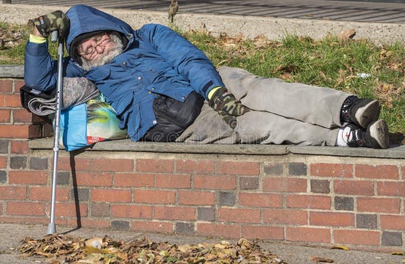 Bezdomny mężczyzna śpi na ścianie z cegieł w parku Boston Massachusetts, Październik - 25, 2018 - obrazy royalty free