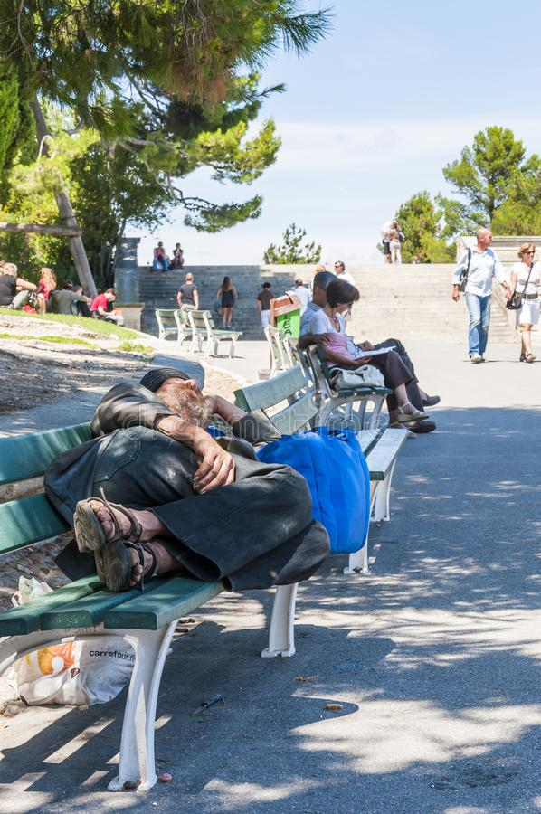 Bezdomny mężczyzna dosypianie na ławce podczas Avignon festiwalu Daleko obrazy stock