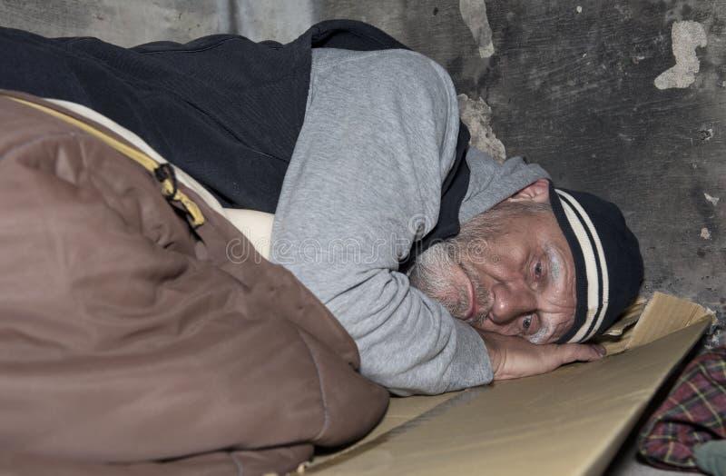 Bezdomny mężczyzna dosypianie na kartonie o i starej sypialnej torbie zdjęcia royalty free
