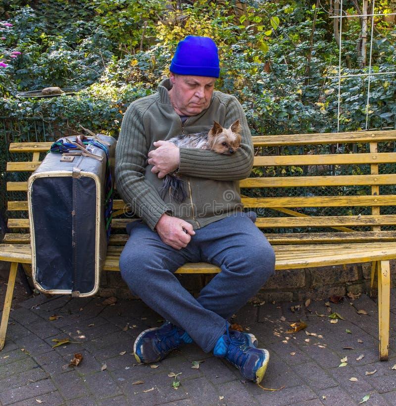 Bezdomny mężczyzna i jego pies siedzimy na parkowej ławce fotografia royalty free