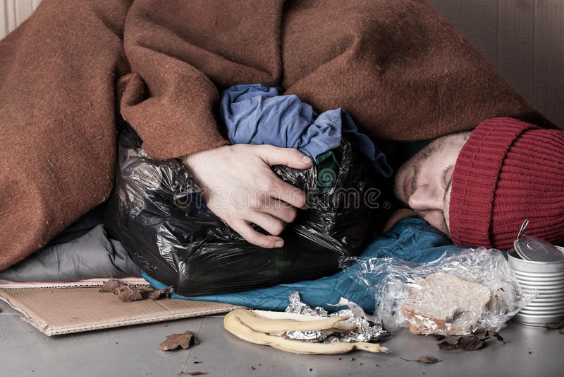 Bezdomny mężczyzna lying on the beach na ulicie zdjęcie royalty free
