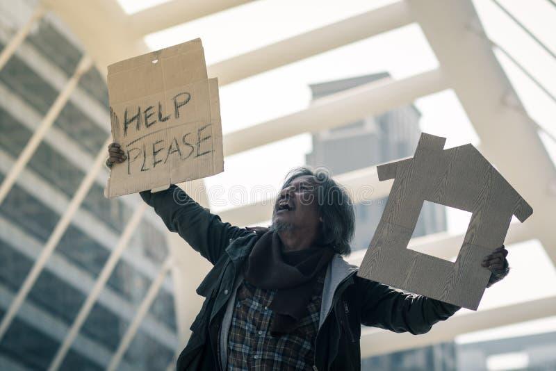 Bezdomny mężczyzna na przejście ulicie w mieście Potrzebuje pomoc od dobroć ludzi zdjęcie stock