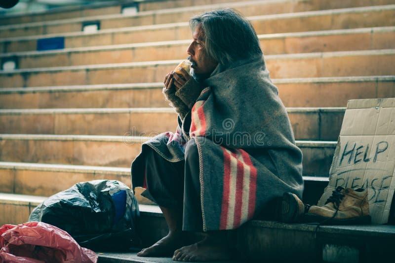 Bezdomny mężczyzna na schodku przejście ulica w miasta łasowania chleba formy dobroci ludziach On chłodno i potrzeby pomoc zdjęcie stock