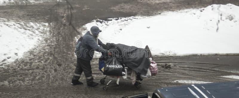 Bezdomny mężczyzna pcha wózek na zakupy z wszystkie jego posiadaniami z brodą obrazy royalty free