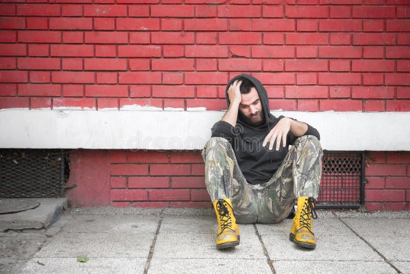 Bezdomny mężczyzny lek, alkohol i uzależniamy się siedzący przygnębiony na ulicie i samotnego zdjęcie royalty free