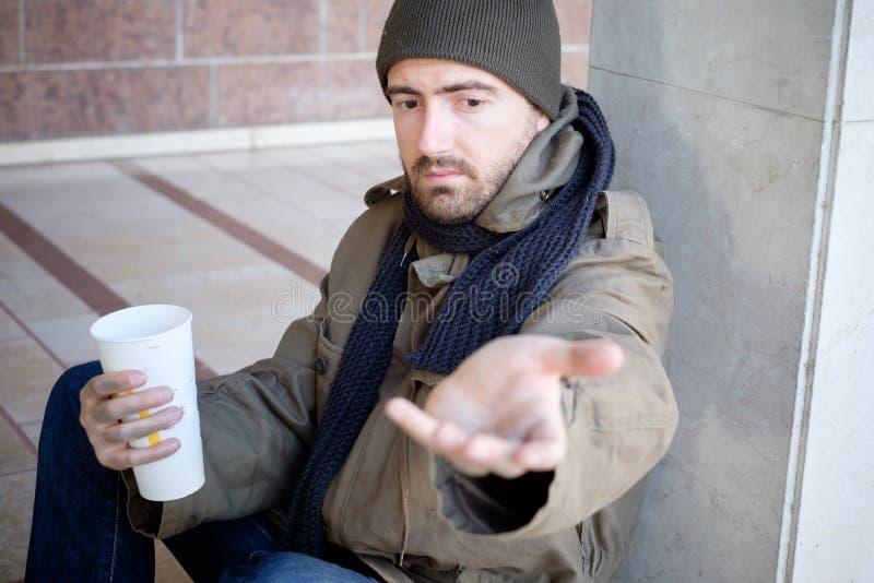 Bezdomny sadzający w ulicie i pytać dla dobroczynności obrazy stock