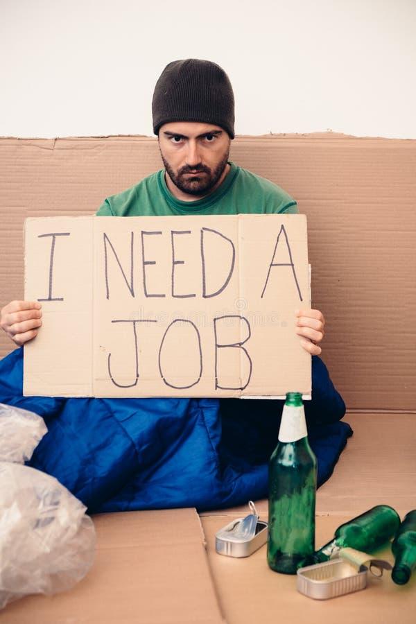 Bezdomny sadzający w ulicie i pytać dla pracy fotografia royalty free