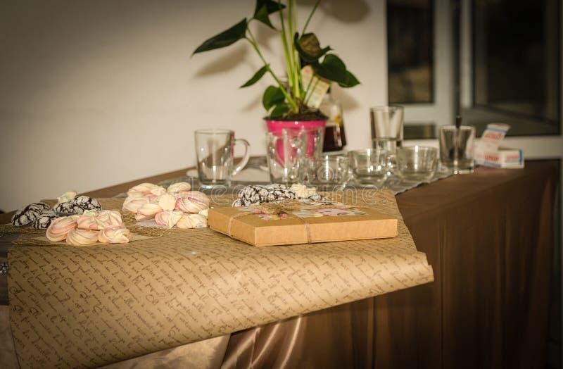 Beze, galletas, pan de jengibre y té en la tabla foto de archivo