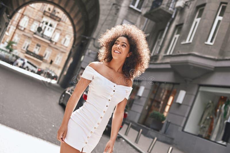 Bezig in de stad Portret van de vrolijke en jonge Amerikaanse vrouw die van Afro in sexy witte kleding terwijl status op a glimla stock foto's