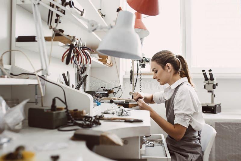 Bezig het werken Zijaanzicht van jonge vrouwelijke juwelier die aan een nieuw juwelenproduct bij haar werkbank werken Juwelen het royalty-vrije stock foto