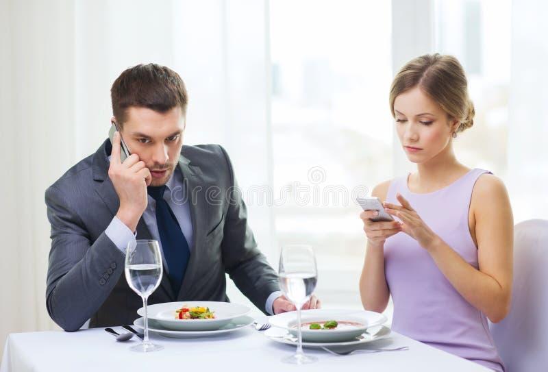 Bezig paar met smartphones bij restaurant stock fotografie