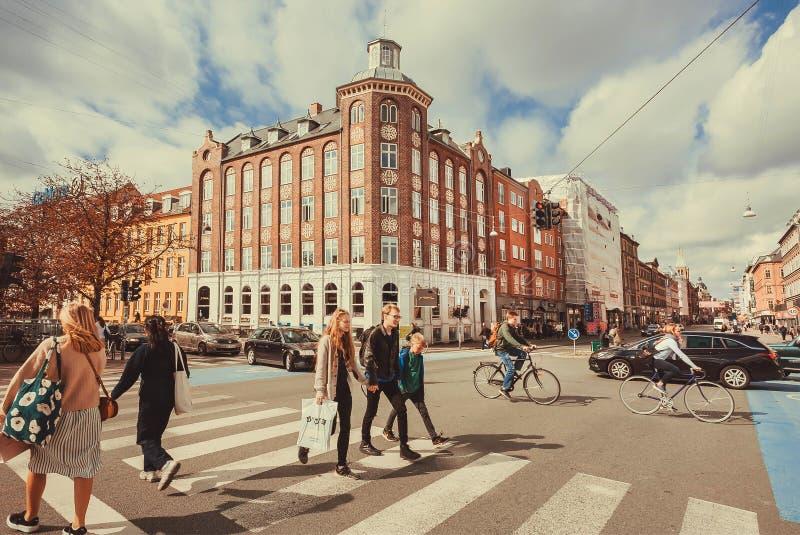Bezig stadscentrum met menigte van mensen en cycli die op kruispunt drijven royalty-vrije stock foto's