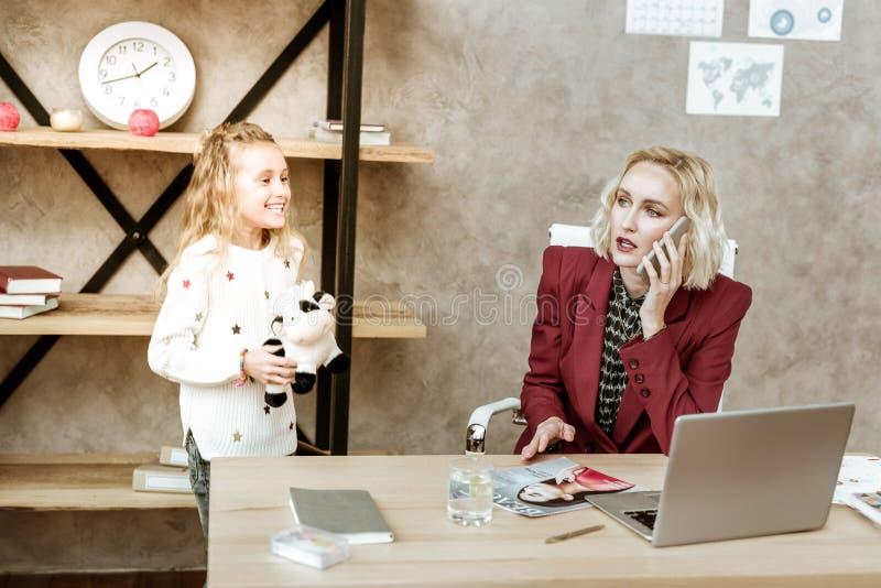 Bezige blondevrouw die op haar smartphone spreken terwijl dochter die zich dichtbij bevinden royalty-vrije stock fotografie