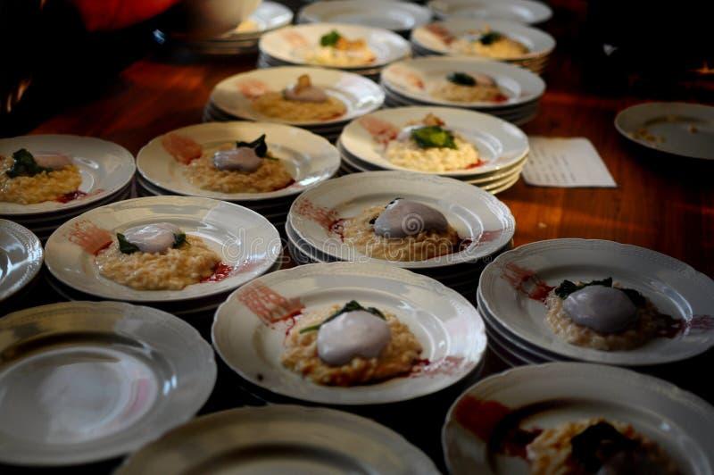 Bezige chef-koks in een restaurant die en betoverend heerlijk voedsel op een houten lijst voor een dinerpartij schikken verfraaie stock foto
