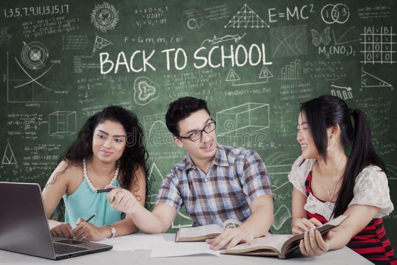 Bezige drie studenten in de klasse stock afbeeldingen