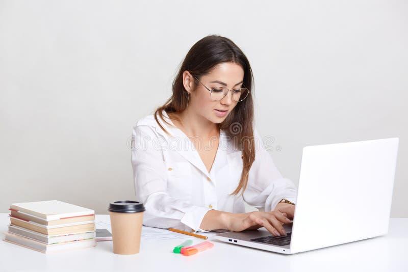Bezige freelancer ontvangt e-mail, koppelen de types op laptop computer terug, draagt om glazen, gekleed in wit die overhemd, met royalty-vrije stock afbeeldingen