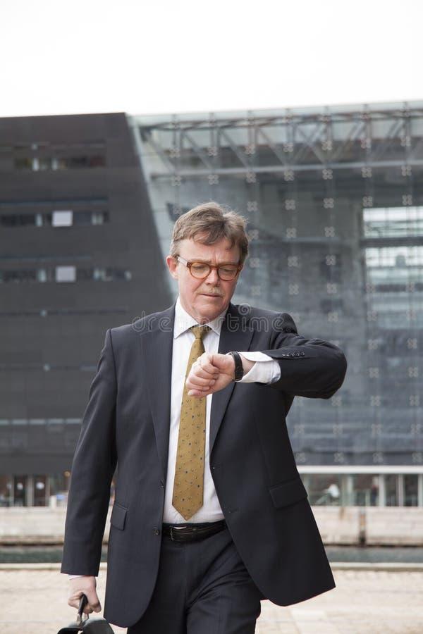 Bezige goed geklede zakenman met aktentas het in hand snel lopen van en het controleren van tijd op zijn polshorloge stock foto