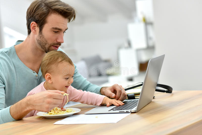 Bezige jonge vader voedende baby en het werken aan laptop stock foto