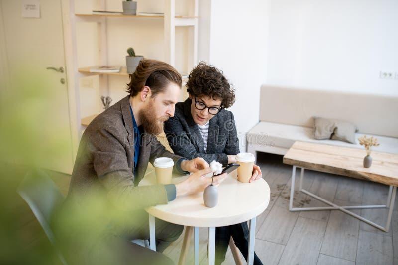 Bezige managers die project in koffie bespreken stock foto's