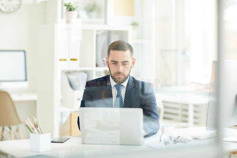 Bezige mens die met laptop werkt royalty-vrije stock foto