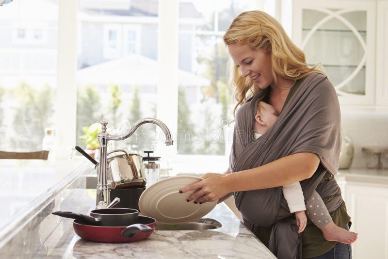 Bezige Moeder met Baby in Slingermultitasking thuis stock afbeeldingen