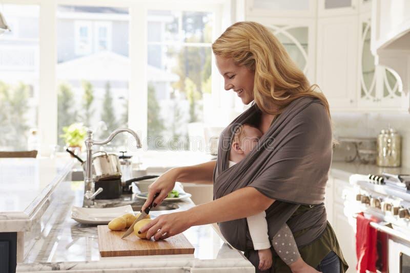 Bezige Moeder met Baby in Slingermultitasking thuis royalty-vrije stock foto's