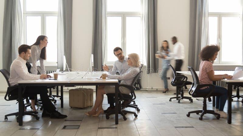 Bezige multiculturele werknemers die aan computers in moderne bureaustormloop werken stock fotografie