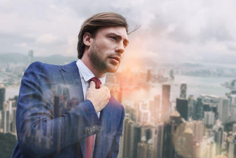 Bezige ochtend Aantrekkelijke bedrijfsdeskundige die zijn stropdas aanpassen terwijl status in openlucht met cityscape op de acht royalty-vrije stock foto's