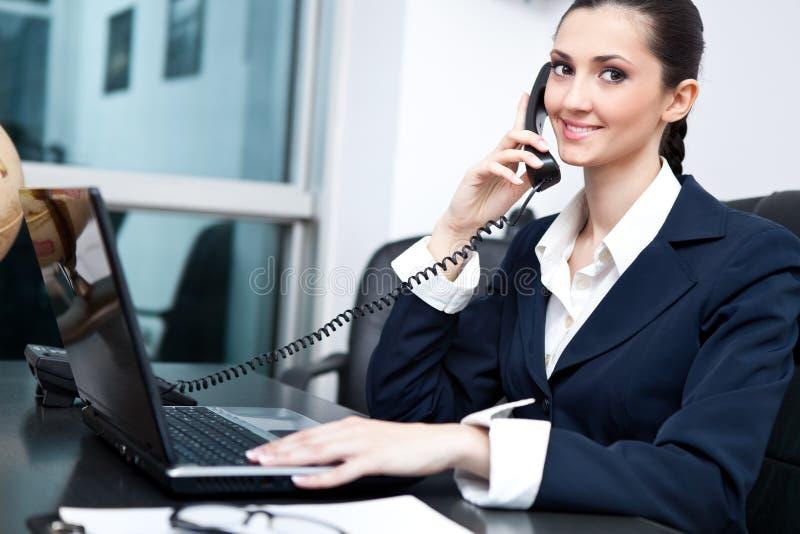 Bezige onderneemster die op telefoon spreekt stock fotografie