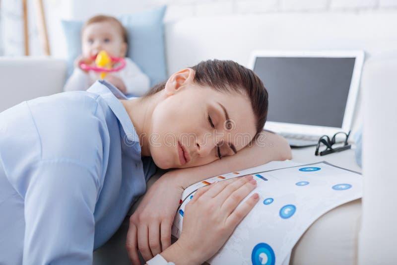 Bezige overweldigde moeder die een dutje nemen stock foto's