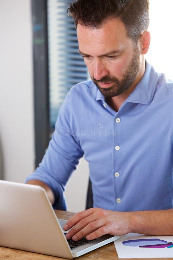 Bezige rijpe mens die aan laptop bij zijn bureau werken stock foto