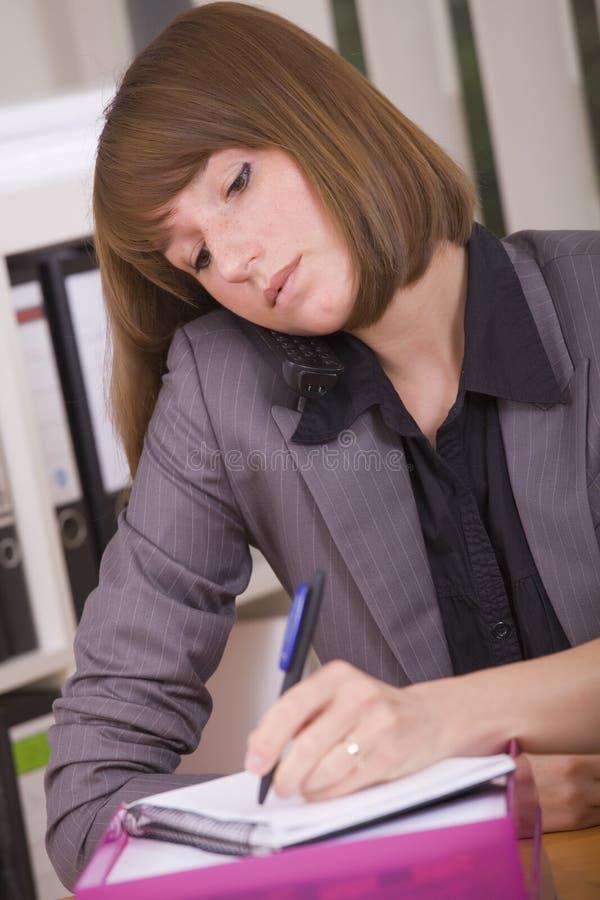 Bezige secretaresse met telefoon stock fotografie