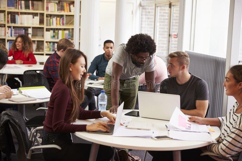 Bezige Universitaire Bibliotheek met Studenten en Privé-leraar stock afbeelding