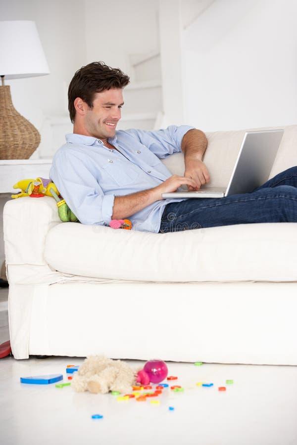 Bezige vader die aan laptop op laag werkt royalty-vrije stock foto
