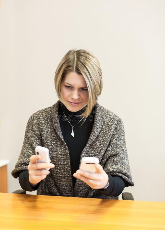 Bezige vrouw die aan twee telefoongesprekken proberen te antwoorden royalty-vrije stock foto