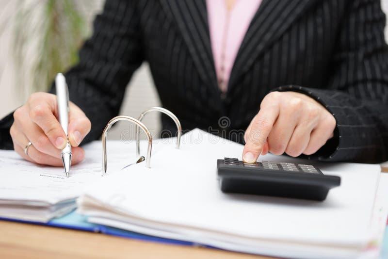 Bezige vrouwelijke accountant die met documenten werken stock foto's