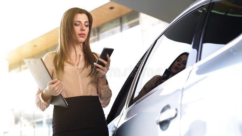 Bezige vrouwelijke ambtenaar van de Openbaar Ministerie die iemand op smartphone roepen, die zich dichtbij auto bevinden royalty-vrije stock foto