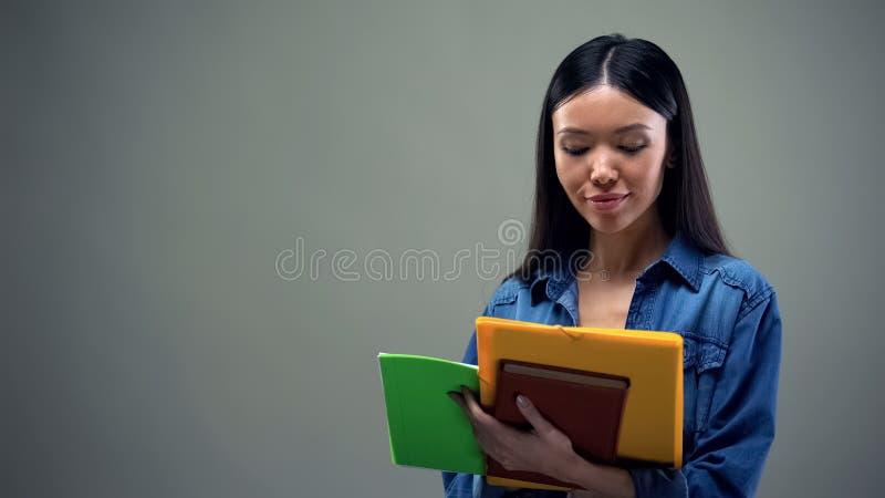 Bezige vrouwelijke holdingsnotitieboekjes en het schrijven programma, het concept van het tijdbeheer stock foto