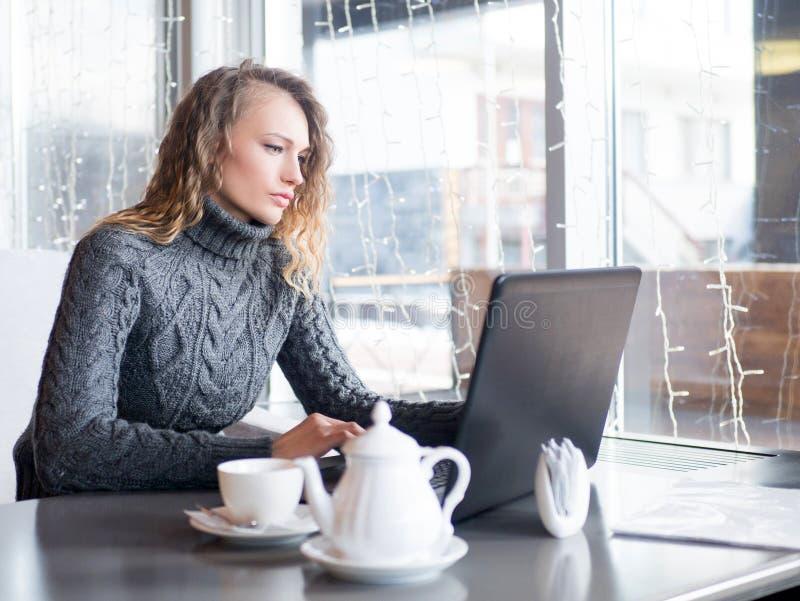 Bezige vrouwelijke student die voor examen in koffie voorbereidingen treffen stock fotografie