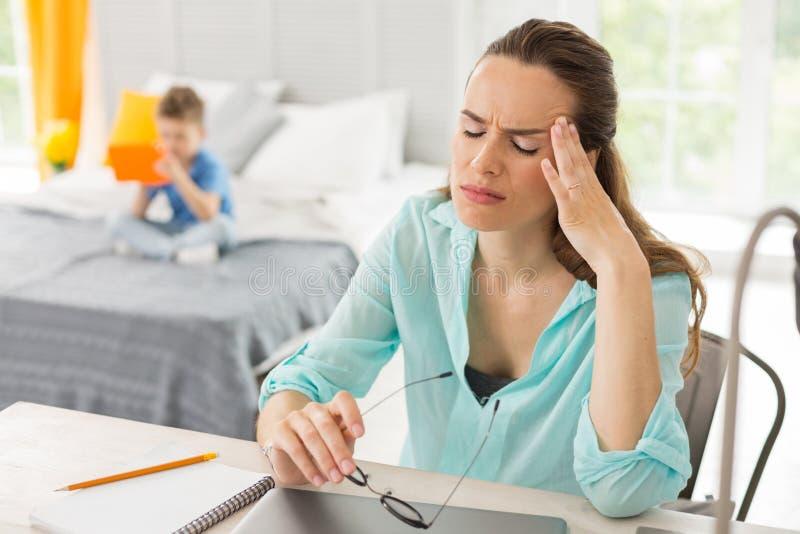 Bezige werkende familievrouw die sterke hoofdpijn hebben stock fotografie