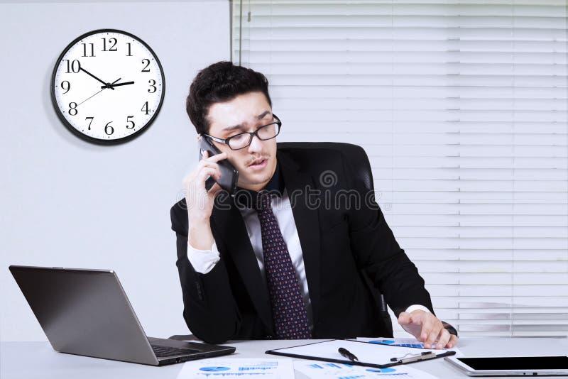 Bezige zakenman met smartphone en administratie stock foto